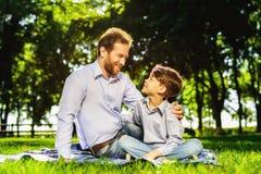 Un hombre y su hijo en un parque en una comida campestre Son feliz Fotografía de archivo libre de regalías