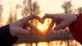 Un hombre y una muchacha en amor llevar a cabo sus manos en la forma de un corazón, un símbolo del amor, contra la perspectiva de almacen de metraje de vídeo