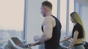 Un hombre y una muchacha están entrenando en una rueda de ardilla en un club de fitness metrajes