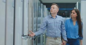 Un hombre y una mujer abrir la puerta del nuevo refrigerador para examinar el diseño y la calidad antes de comprar en un consumi almacen de video