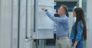 Un hombre y una mujer abrir la puerta del refrigerador examinan el diseño y la calidad antes de comprar en la tienda almacen de metraje de vídeo