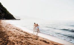 Un hombre y una mujer alegres que caminan en la playa el vacaciones de verano Copie el espacio fotografía de archivo libre de regalías