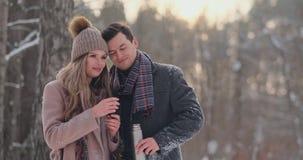 Un hombre y una mujer cariñosos de los pares en el té de consumición del bosque del invierno de un termo Hombre y mujer elegantes metrajes