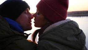 Un hombre y una mujer cariñosos de los pares que se besan al aire libre en la caída en la puesta del sol cámara lenta, 1920x1080, almacen de metraje de vídeo