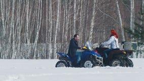 Un hombre y una mujer del bosque A del invierno que se sientan en motos de nieve y que se dan altos cinco almacen de metraje de vídeo