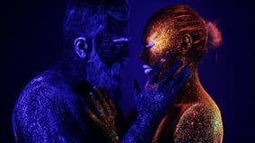 Un hombre y una mujer en la luz ultravioleta se acarician Fuego e hielo, dos hypostases almacen de video