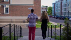 Un hombre y una mujer en los deportes que el traje se dedica a deportes en el ambiente urbano, ellos corren a lo largo de la call almacen de metraje de vídeo