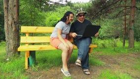 Un hombre y una mujer en un parque en un banco con un ordenador portátil leyeron los tebeos almacen de video