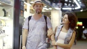 Un hombre y una mujer felices están caminando en el mercado de la tarde Un par el vacaciones fue a hacer compras, él elige recuer almacen de metraje de vídeo