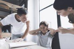 Un hombre y una mujer gritan airadamente en una pequeña muchacha oscuro-cabelluda que se siente en un escritorio cerca de la vent Fotos de archivo