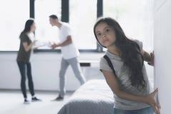 Un hombre y una mujer juran adentro el cuarto La muchacha oscuro-cabelluda intenta escaparse imperceptiblemente del apartamento Fotografía de archivo libre de regalías
