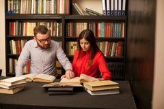 Un hombre y una mujer leyeron los libros en la biblioteca se están preparando para el examen 1 fotos de archivo