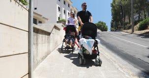 Un hombre y una mujer llevan los cochecitos de niño con los niños de vacaciones en el verano almacen de video