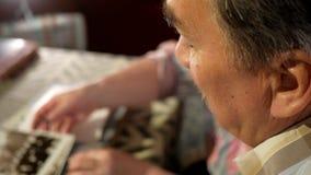 Un hombre y una mujer mayores de los pares están mirando sus fotos viejas en casa y hablar Un hombre con un bigote, esposa con almacen de metraje de vídeo