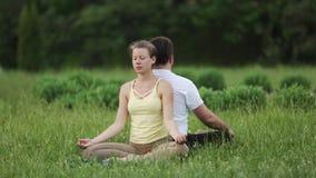 Un hombre y una mujer meditan en dicha Los instructores jovenes de la yoga practican en un parque de la ciudad en hierba verde Jó almacen de metraje de vídeo