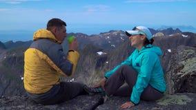 Un hombre y una mujer se están sentando encima de una roca metrajes