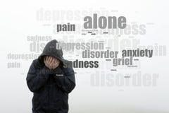 Un homme à capuchon tenant sa tête dans des ses mains Avec un nuage de mot des enjeux de la santé mentale Sur un fond blanc simpl images stock