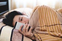 Un homme à l'aide du téléphone intelligent le matin, vérifiant le message après s'être réveillé photographie stock libre de droits