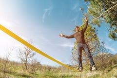 Un homme, âgé avec une barbe et des lunettes de soleil de port, équilibre sur un slackline en plein air entre deux arbres au couc Images libres de droits