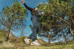 Un homme, âgé avec une barbe et des lunettes de soleil de port, équilibre sur un slackline en plein air entre deux arbres au couc Images stock