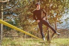 Un homme, âgé avec une barbe et des lunettes de soleil de port, équilibre sur un slackline en plein air entre deux arbres au couc Photo stock