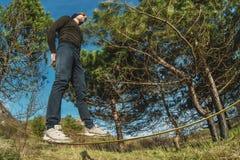 Un homme, âgé avec une barbe et des lunettes de soleil de port, équilibre sur un slackline en plein air entre deux arbres au couc Photos stock