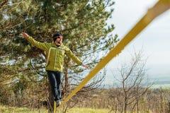 Un homme, âgé avec une barbe et des lunettes de soleil de port, équilibre sur un slackline en plein air entre deux arbres au couc Photo libre de droits