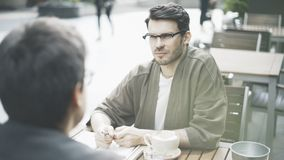 Un homme écoutant son ami dans un café dehors Images stock