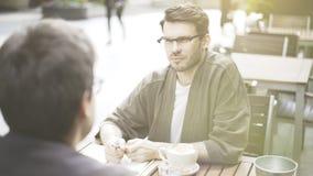 Un homme écoutant son ami dans un café dehors Photos libres de droits
