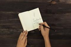 Un homme écrit dans un carnet qui se trouve sur un arbre Image libre de droits