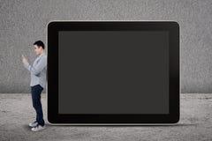 Un homme écrit SMS et se tenir prêt un grand comprimé Photos stock