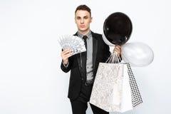 Un homme élégant, dans un costume noir, tenant des sacs, pour faire des emplettes, et photo stock