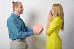 Un homme élégant dans une chemise verte à carreaux donne à une belle fille mince dans une robe jaune un boîte-cadeau sous forme d Image libre de droits