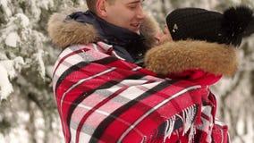 Un homme étreint doucement son épouse pendant l'hiver dehors banque de vidéos