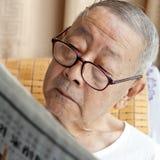Un homme aîné est journal du relevé Photo stock