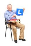 Un homme aîné s'asseyant sur une présidence retenant un L plaque Images stock