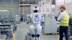 Un homme active le droid à une usine Un travailleur branche un robot pour le faire tirer un chariot lourd avec des feuillards