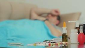 Un homme adulte avec des symptômes de maladie dort sur le divan sous le couvert d'une couverture banque de vidéos