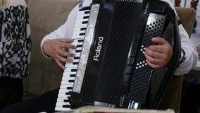 Un homme adulte joue un accordéon dans un costume national Jouer musical de quartet Les musiciens exécutent au concert E clips vidéos