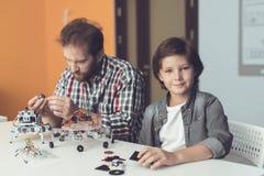 Un homme aide un garçon avec un ensemble de robot Le garçon regarde l'appareil-photo tandis que l'homme assemble le robot Photo libre de droits