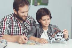 Un homme aide un garçon avec un ensemble de robot Les montres d'un homme en tant que garçon finit d'assembler le robot Photographie stock libre de droits