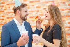 Un homme alimente à une fille par morceau de pizza Photographie stock libre de droits