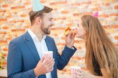 Un homme alimente à une fille par morceau de pizza Photo stock