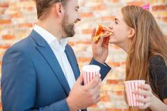 Un homme alimente à une fille par morceau de pizza Photographie stock