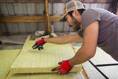 Un homme asiatique chauffant sa maison utilisant la laine de laitier Image libre de droits