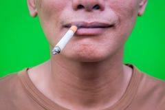 Un homme asiatique fumant sur le fond vert Photo libre de droits