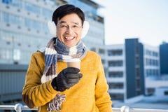 Un homme asiatique plus âgé avec du café à aller Photo libre de droits