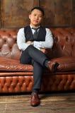 Un homme asiatique réussi s'assied sur un divan en cuir, mettant son pied sur sa jambe images stock