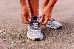 Un homme attachant des dentelles sur des chaussures de sports Seulement mains et pieds étroitement photographie stock