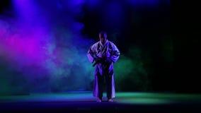 Un homme attache une ceinture noire de karaté sur un fond de fumée colorée Et étant prêt pour faire le kata clips vidéos